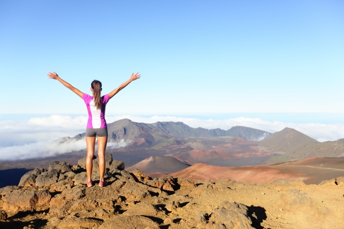 Woman Runner celebrating on top of a mountain